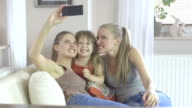 Three cute girl in different age at home holding up a smartphone to take a picture video