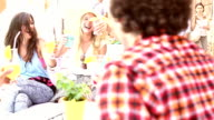 Three female friends drinking cocktails on terrace cafe in summer video