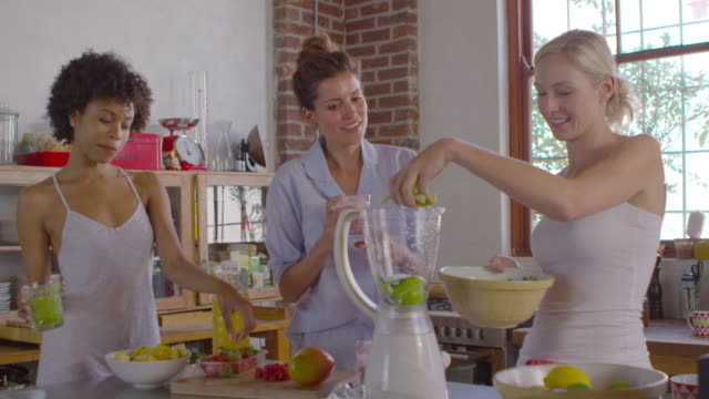 Three female friends making smoothies in kitchen, shot on R3D video