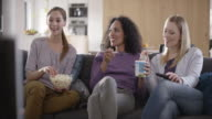Three female friends talking on the sofa while watching TV video