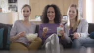 Three female friends talking while watching TV and eating popcorn video