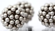Three figures consisting of metallic balls rotate around its axis video