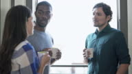 Three friends, girl and two guys, have conversation and drink coffee next to the open window video