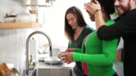 Three friends on the kitchen. Young man coming in and surprising his girlfriend. video