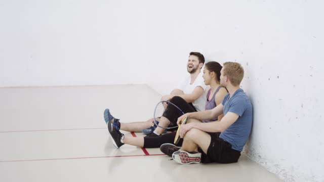 Three friends sitting on floor of racquetball court video