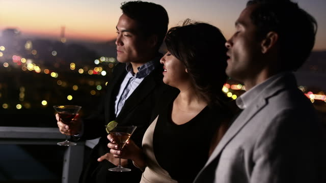 Three friends stand on a rooftop bar at sunset and admire the scenery with drinks in hand and then toast video
