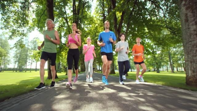 SLO MO TS Three generation family jogging in a beautiful park video