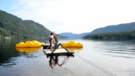 Three generation family pulling a wooden raft on the lake in mountains video
