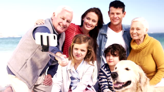 Three generations family with dog taking selfie video