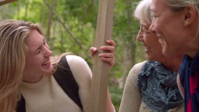 Three generations of woman laughing in a forest, slow motion video