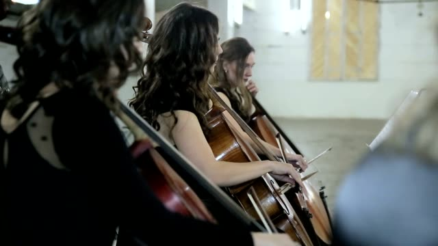 Three girl play on violoncello in orchestra video