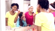Three girls at sleepover putting on makeup video