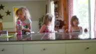 Three girls sitting at a kitchen counter in the morning video