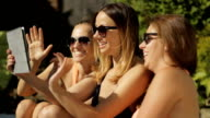 Three girls talking by tablet on summer vacation video