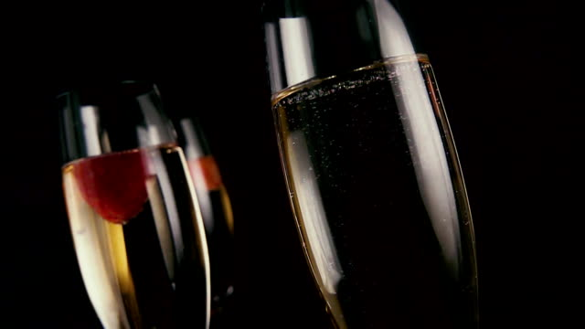 Three glasses with champagne and strawberries. Slow mo video