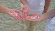 Three Hands Holding Breast Cancer Awareness Ribbon video