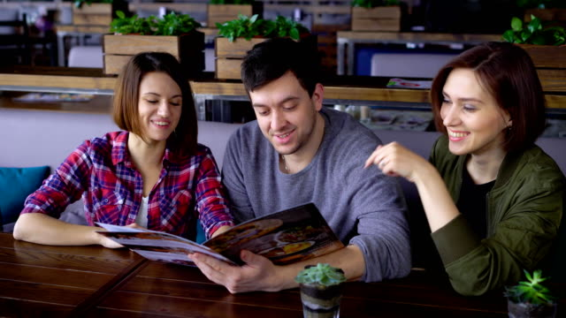 Three happy friends sitting in cafe reading menu and choosing food and beverages. Two women and one man spending lunch time together in restaurant discussing their future order video