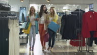 Three happy girls are walking through a clothing store in colorful garments. video