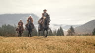 SLO MO Three herdsmen galloping across mountain meadow video