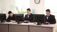 Three identical businessmen working in office video