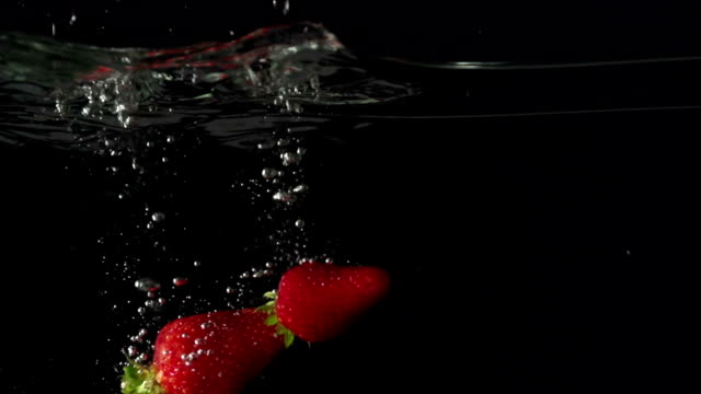 Three juice strawberryes splashing into water in slowmotion video