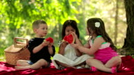 Three kids have fun eating fruit together video