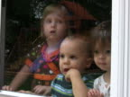 Three Kids looking through glass with rain NTSC video