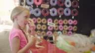 Three little girls playing a bean bag toss at a fair video