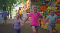 Three little girls running toward the camera at a carnival, slow motion video