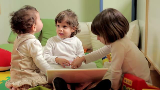 Three little girls using laptop computer video