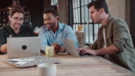 Three Male Designers In Meeting Using Laptop video