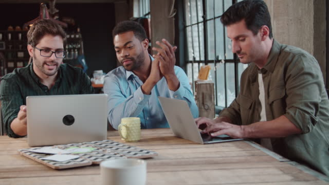 Three Male Designers In Meeting Using Laptops video
