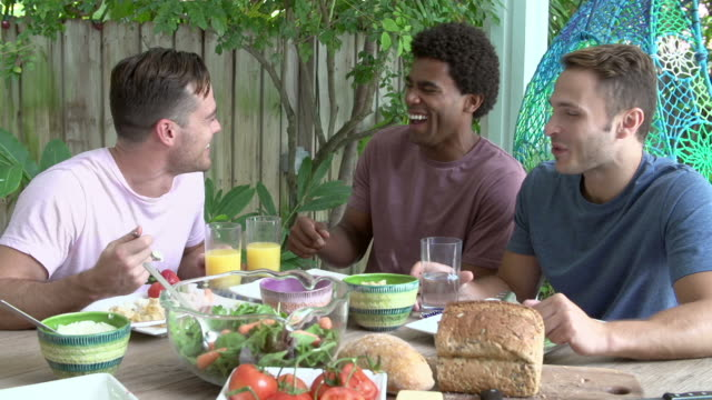 Three Male Friends Enjoying Meal Outdoors At Home video