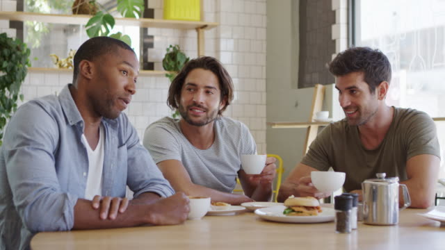Three Male Friends Meeting In Coffee Shop Shot In Slow Motion video