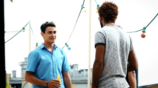 Three male friends talking and drinking at the rooftop video