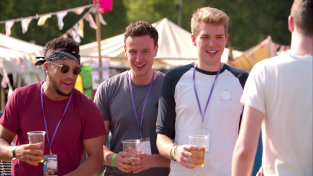 Three male friends walking at a music festival, slow motion video
