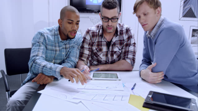 Three male startup colleagues checking the design plan video