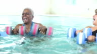 Three mature women talking, doing water aerobics video