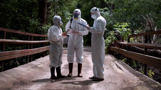 Three men in biohazard suits standing on a bridge video