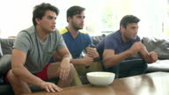 Three Men Sitting On Sofa Watching TV Looking Disappointed video