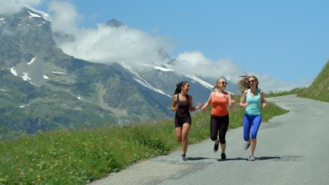 Three multi ethnic adult women running down a stunning mountain road. video