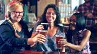 Three multi-ethnic girlfriends drinking beer in bar video