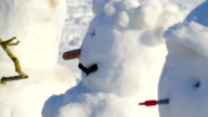 Three of the many snowman on the roadside video