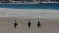 Three people horse back riding on Long Beach in Noordhoek, Cape Town, South Africa on hot, hazy day video