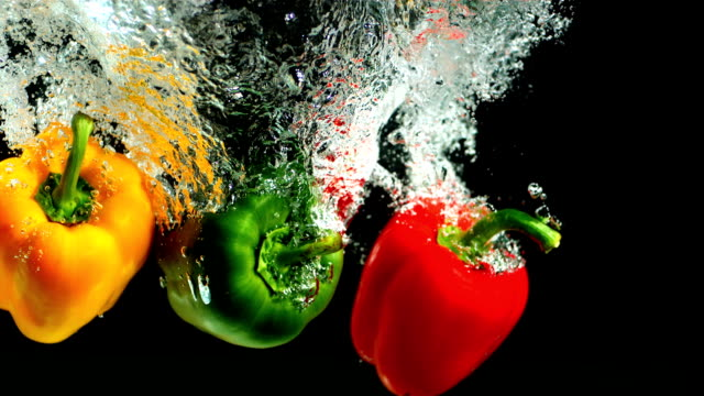 Three peppers falling into water and floating video