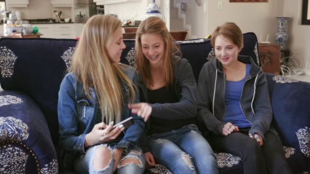 Three pretty young teenage girls sitting on a sofa, taking a selfie video and having fun video