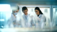 Three scientists working in a research laboratory video