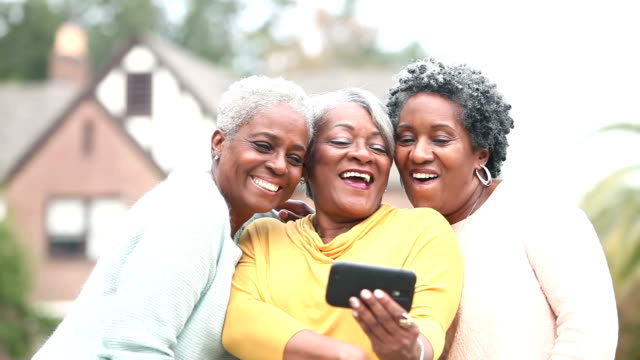 Three senior African American women taking a selfie video