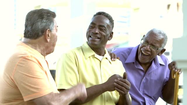 Three senior men sitting on bench, talking, laughing video