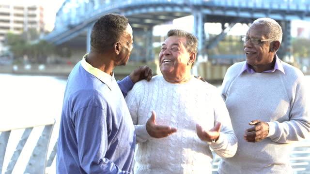 Three senior men talking, laughing outdoors video